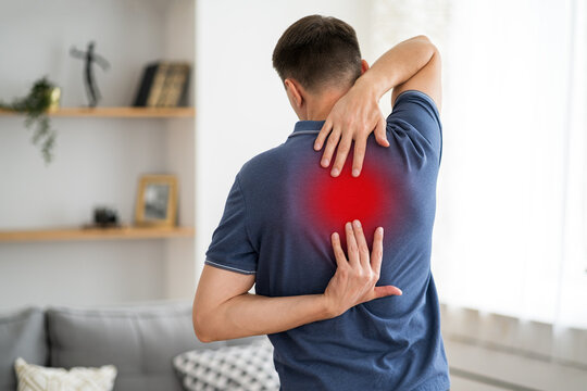 Pain between the shoulder blades, man suffering from backache at home