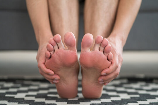 Foot pain, man suffering from feet ache at home