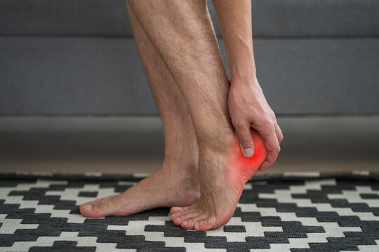 Heel spur, foot pain, man suffering from feet ache at home