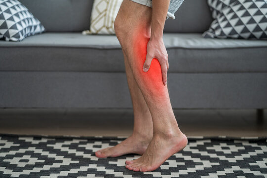 The man's calf muscle cramped, massage of male leg at home