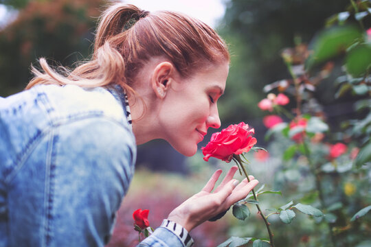 Young redhead Caucasian woman smelling rose in park