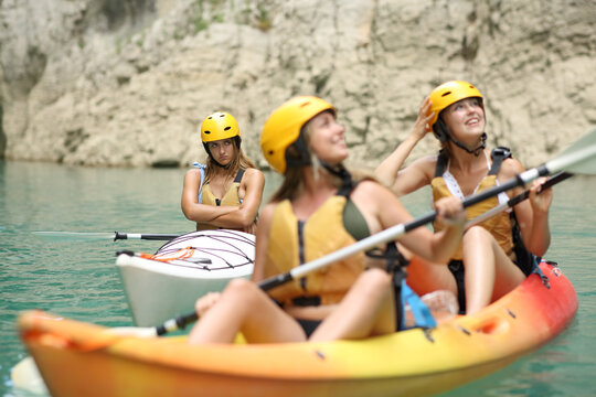 Excluded angry woman being ignored by her friends in a kayak