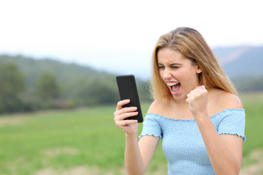 Excited teen checking content on smart phone in a field