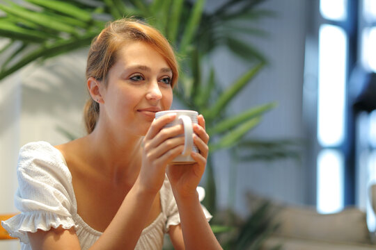 Happy woman drinking coffee at home looking away