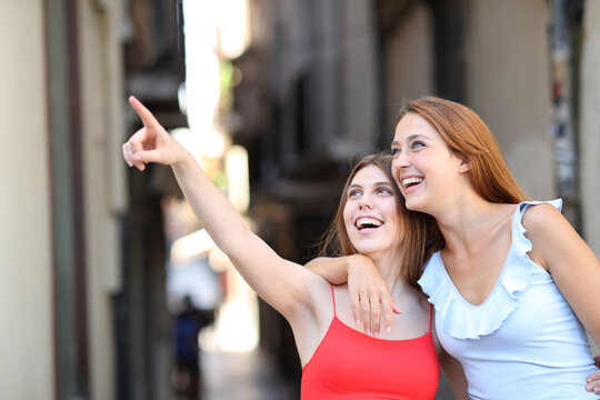 Two happy friends pointing up in the street