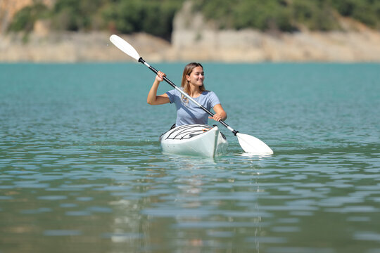 Happy woman in a kayak rowing in a lake