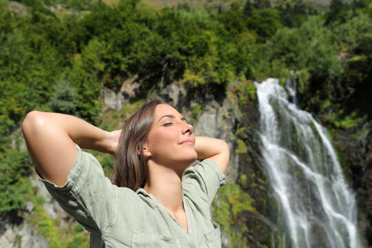Happy woman breathing and resting in a waterfall