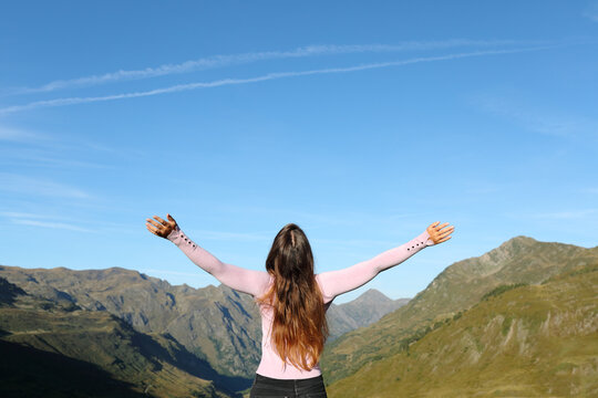 Single woman outstretching arms in the mountain