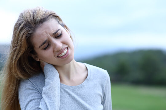 Teen suffering neck ache in a field