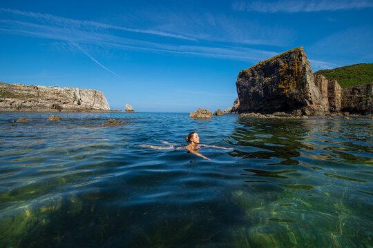 Happy woman swimming in a beautiful beach