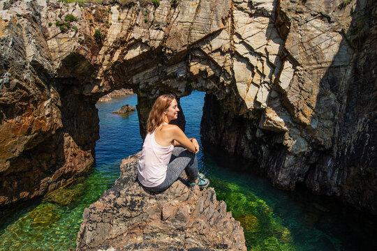 Trekker woman sitting in a beach contemplating