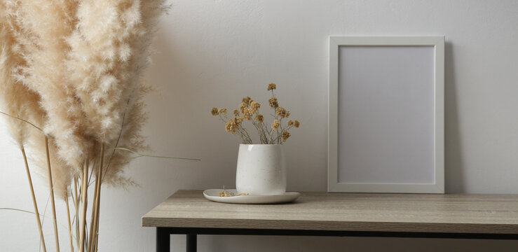 Horizontal white frame mockup on table with ceramic vase with yellow dry Everlasting flowers. White wall background.