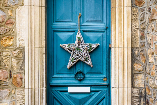Front view of a star-shape Christmas decoration made of branches and pine cones, hanging on the blue front door with moldings of an old townhouse.