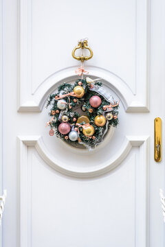 Front view of a Christmas crown made of plastic fir branches with baubles and ribbons, hanging on a white front door with moldings.