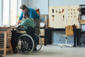 Obraz Full length side view portrait of young man in wheelchair learning leathermaking craft in leatherworkers workshop, copy space - fototapety do salonu
