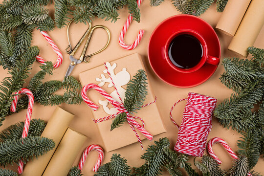 Christmas composition. gift box wrapped in craft paper, fir tree branches, candy canes. new year concept. Greeting card, xmas celebration 2022. Flat lay, top view, copy space, mockup
