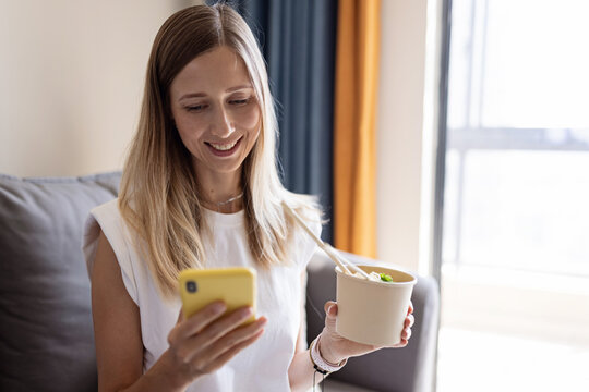 Young caucasian business Woman with blonde hair wearing casual clothing and has a lunch from paper plate with healthy food for wellbeing and keto diet. Fast food delivery to home. Work from home