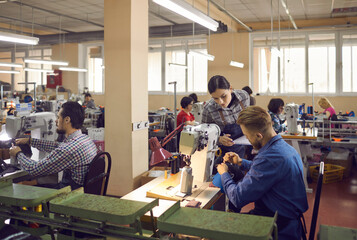 Obraz People working in a big workshop room at a shoe factory. Male and female workers sitting at tables with industrial sewing machines and making new footwear details. Manufacturing industry concept - fototapety do salonu