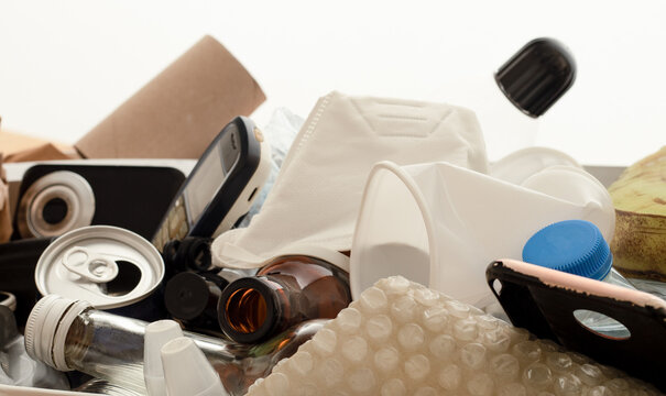 Electronic, glass, metal, paper, plastic and organic  waste materials collected in white box. Waste management concept.