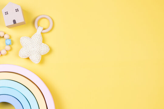 Baby kid toys on yellow background. Sustainable early childhood development baby stuff and pastel color wooden toys