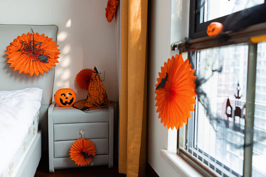Home decor for Halloween celebration with paper garland orange color, bat on window
