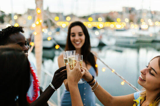 Happy multiracial young people cheering with champagne on a boat during christmas holidays - Millennial friends celebrate birthday together - Friendship, eve and celebration concept. Focus on glasses