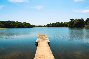 isolated lonely wooden pier over clam tranquil lake water with trees and blue sky