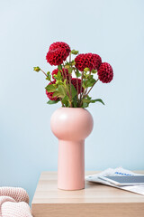 Obraz Vase with beautiful dahlias, newspapers and tablet computer on table in room - fototapety do salonu