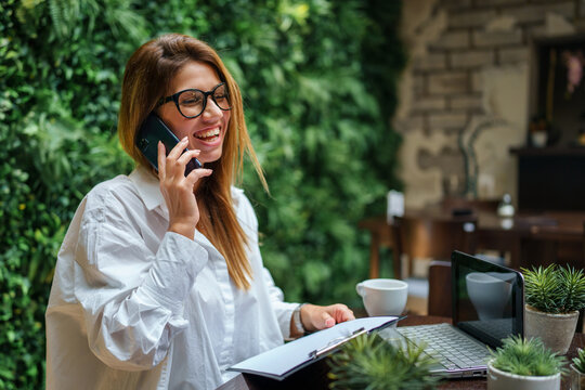 Adult caucasian businesswoman working on laptop computer and making a phone call while sitting at the table at cafe happy smiling female woman entrepreneur concept