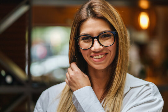Front view of beautiful caucasian woman wearing white shirt and eyeglasses looking to the camera smiling close up copy space real people