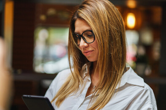 Front view portrait of adult caucasian woman female entrepreneur holding mobile phone reading messages or making a video call while standing at office or cafe copy space