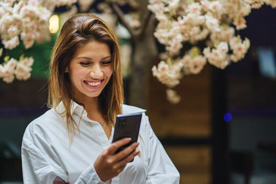 Front view portrait of adult caucasian woman female entrepreneur holding mobile phone reading messages or making a video call while standing at office or cafe smiling happy copy space