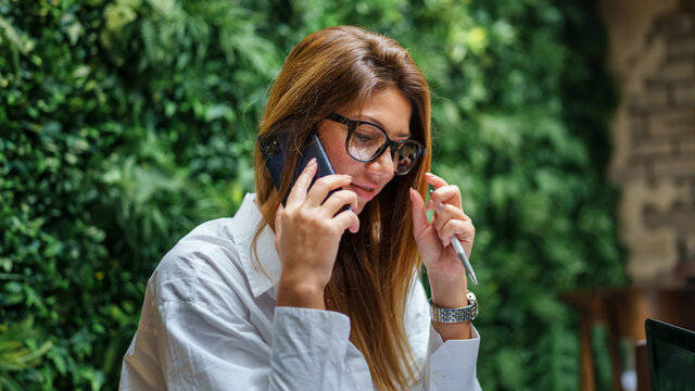 Side view of adult beautiful female entrepreneur making a phone call woman holding mobile phone and pencil while talking copy space