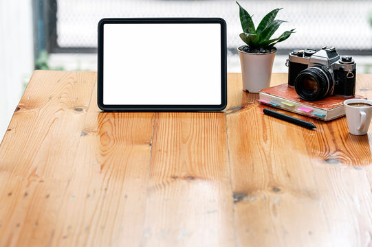 Blank screen portable tablet and camera on wooden table with copy space.