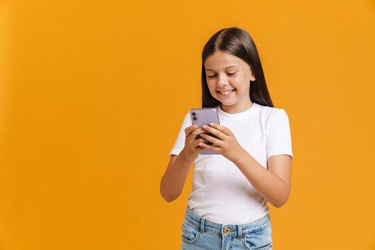 White brunette girl smiling while using mobile phone