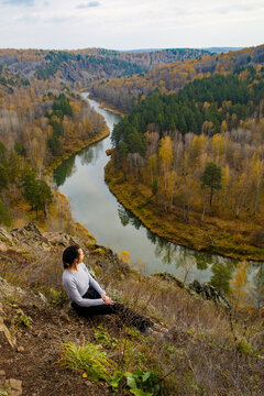 Woman hiker sitting on rock on top of mountain watching beautiful scenery of backcountry of Berd river, Novosibirsk region, Russia. Location: Zveroboy trail, Berdskie skaly, Novosibirsk, vertical
