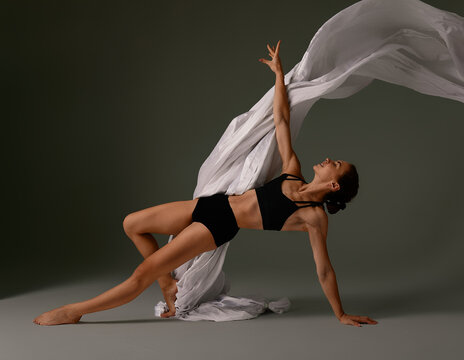 Emotional Female Ballet Dancer in Body Suit and Flying material Posing in Dance in Various Poses Against Gray Background