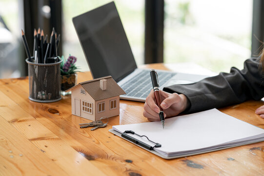 Cropped image of woman hand holding pen writing on blank paper with house model and keys.