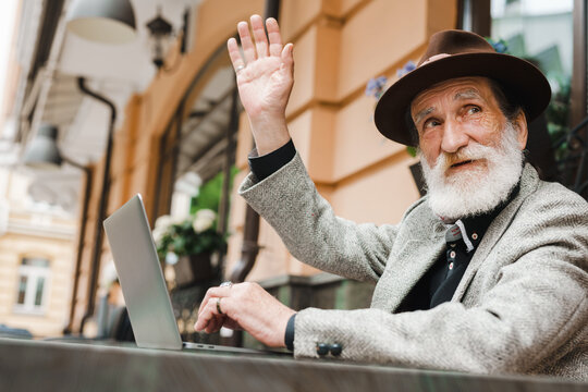White senior man gesturing while working with laptop in cafe