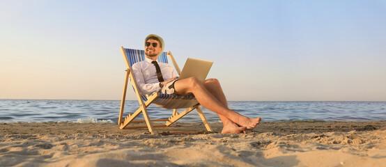 Obraz Happy man with laptop resting on deckchair near sea. Business trip - fototapety do salonu