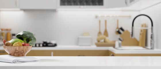 Obraz White kitchen countertop with vegetables bowl, napkin and space for montage on blurred modern bright kitchen - fototapety do salonu