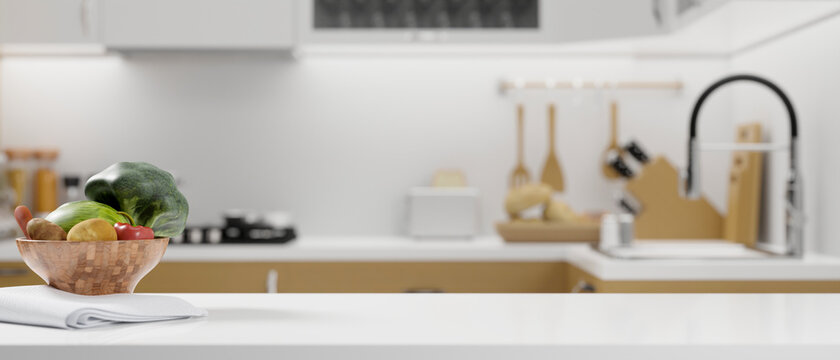 White kitchen countertop with vegetables bowl, napkin and space for montage on blurred modern bright kitchen