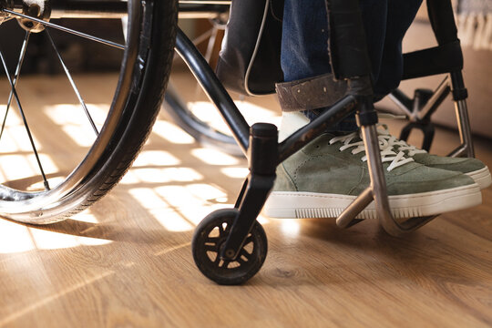 Low section of disabled man sitting on wheelchair using smartphone at home