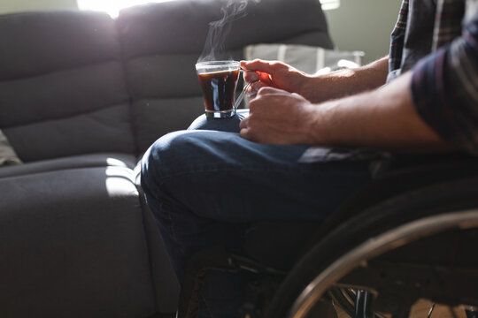 Mid section of disabled man sitting on wheelchair holding coffee cup at home