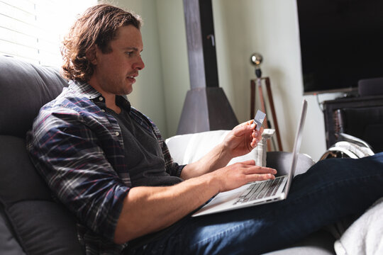 Caucasian disabled man holding a credit card using laptop sitting on the couch at home
