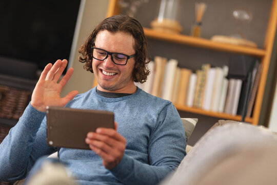Caucasian disabled man wearing glasses waving while having a video call on digital tablet at home