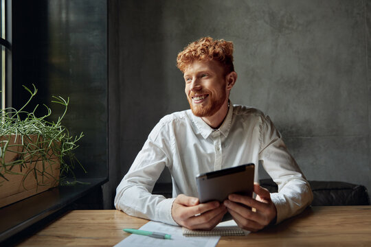 Happy man in white shirt using tablet on desk