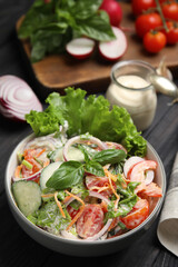 Obraz Bowl of delicious vegetable salad dressed with mayonnaise and ingredients on black table - fototapety do salonu