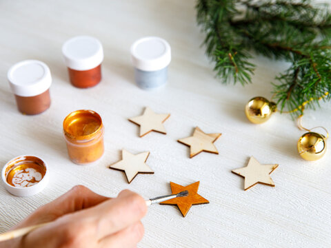 The process of painting wooden Christmas decoration - five stars. Decoupage process. Preparation for New year or Christmas concept background. Selective focus, top view