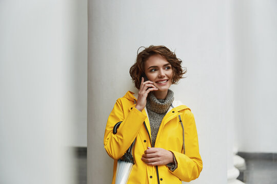 Woman in yellow raincoat with smartphone in hand